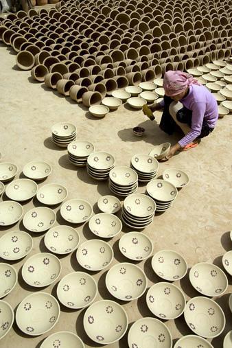 Fazekasműhely udvarán, díszítik a tálakat (China, Xinjiang, 2006.08.11.)